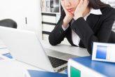 退屈な日常と成長実感のない環境のイメージ画像。オフィスにいる女性が自分の席に座り、PCの前で頬杖をついている。