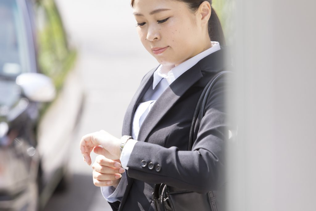 インターンに遅刻し、時計を見る就活生のイメージ