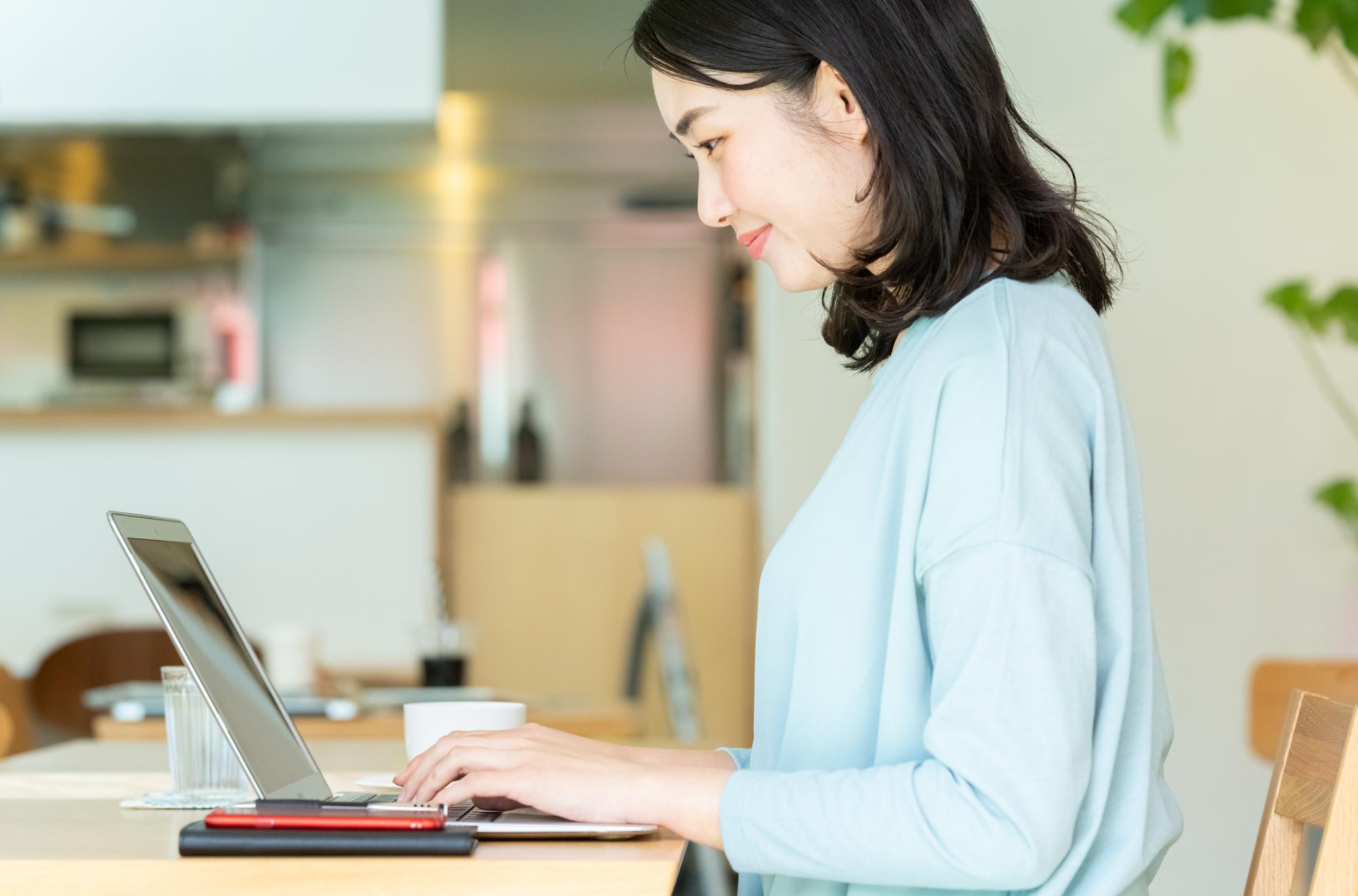 カフェでパソコンを使い、仕事をしている女性