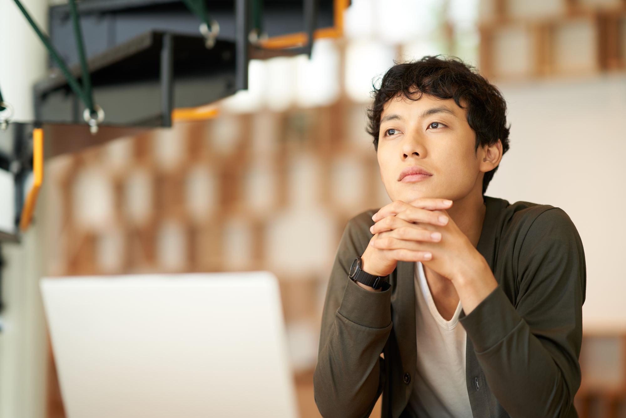 パソコンの前で考え事をしている男性