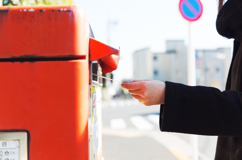 郵便ポストに企業への書類を投函するイメージ